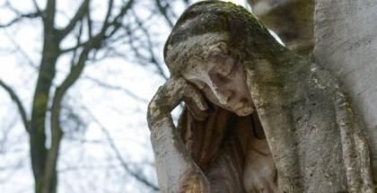 פסל עתיק מאבן של אישה המניחה את ראשה על ידה
