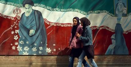 שתי נשים איראניות חולפות על פני גרפיטי מהפכני באיראן