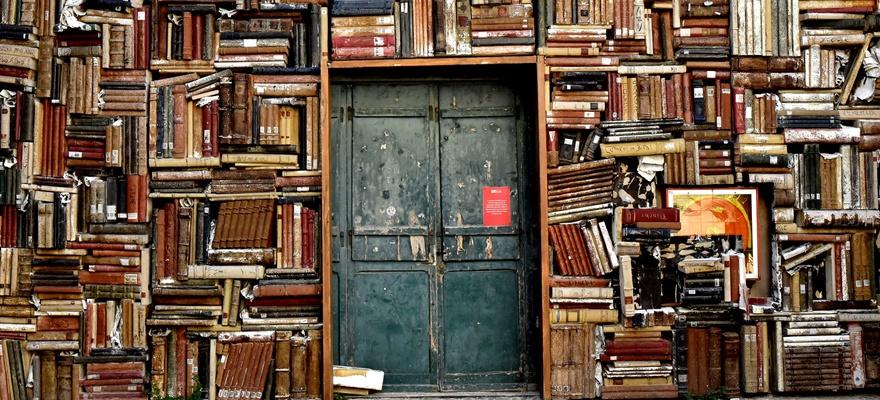 דלת ספריה משובצת בקיר ספרים ישנים