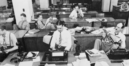 מערכת עיתון הניו יורק טיימס בתחילת המאה הקודמת אנשים יושבים מול מכונות כתיבה וטלפונים. התמונה בשחור לבן.